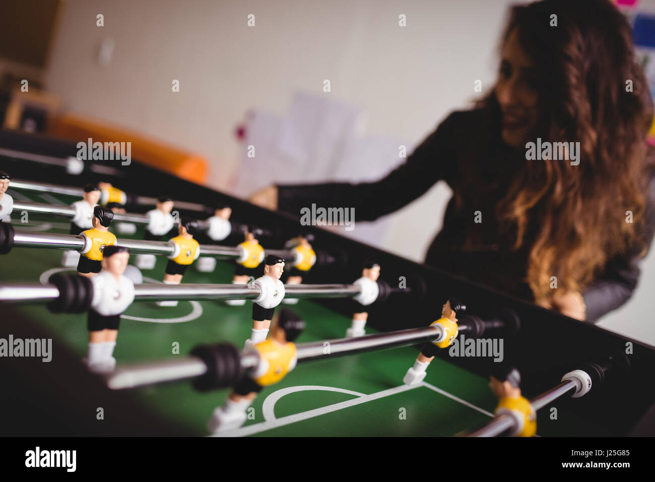 Concentrated woman playing table football game - Stock Image