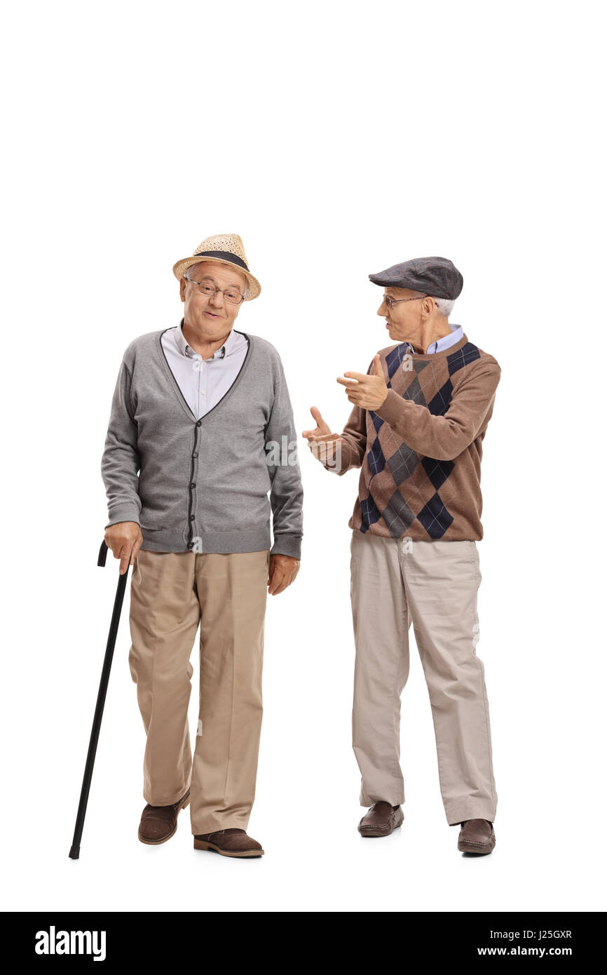 Full length portrait of two elderly men walking towards the camera and talking to each other isolated on white background - Stock Image