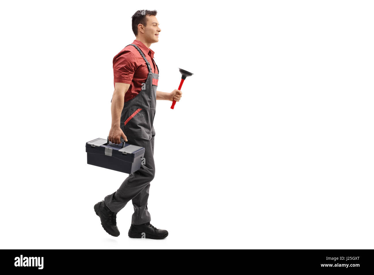 Full length profile shot of a plumber holding a plunger and a toolbox walking isolated on white background - Stock Image
