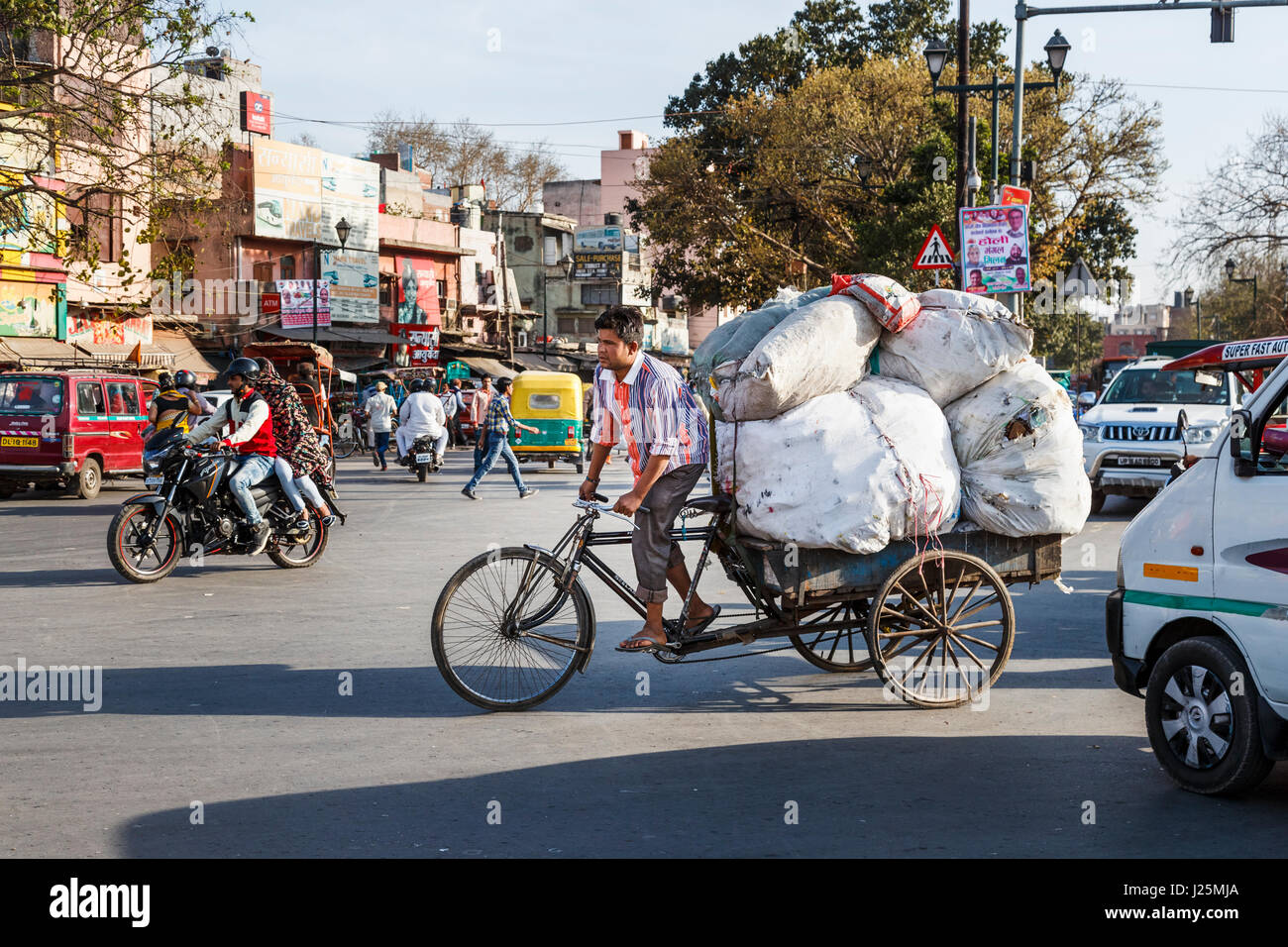Local Indian man pedalling a tricycle carrying a large heavy load of sacks at a road junction in a busy street in - Stock Image