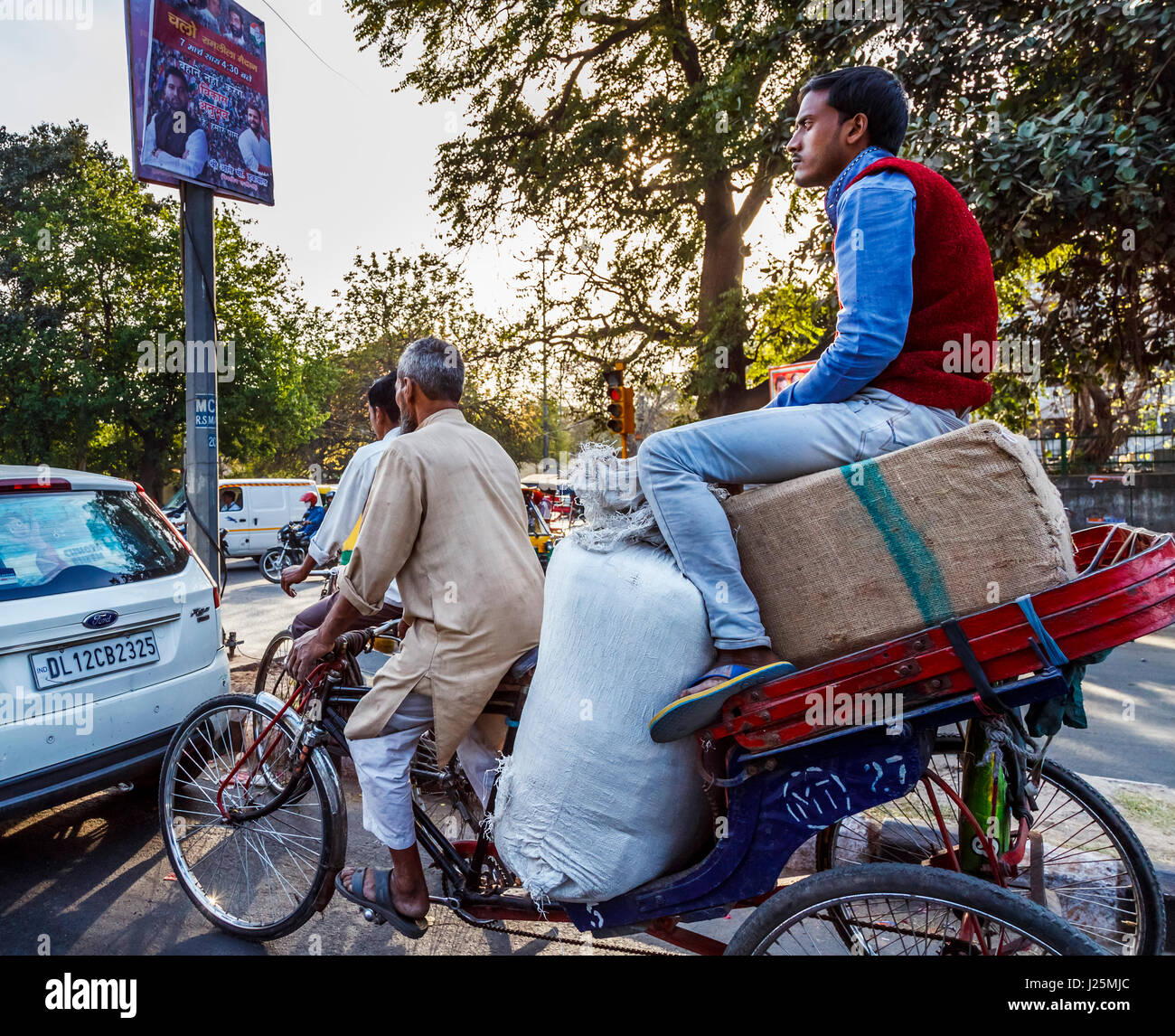 Local Indian man pedalling a tricycle rickshaw, passenger sitting on a large load of sacks at a road junction in - Stock Image