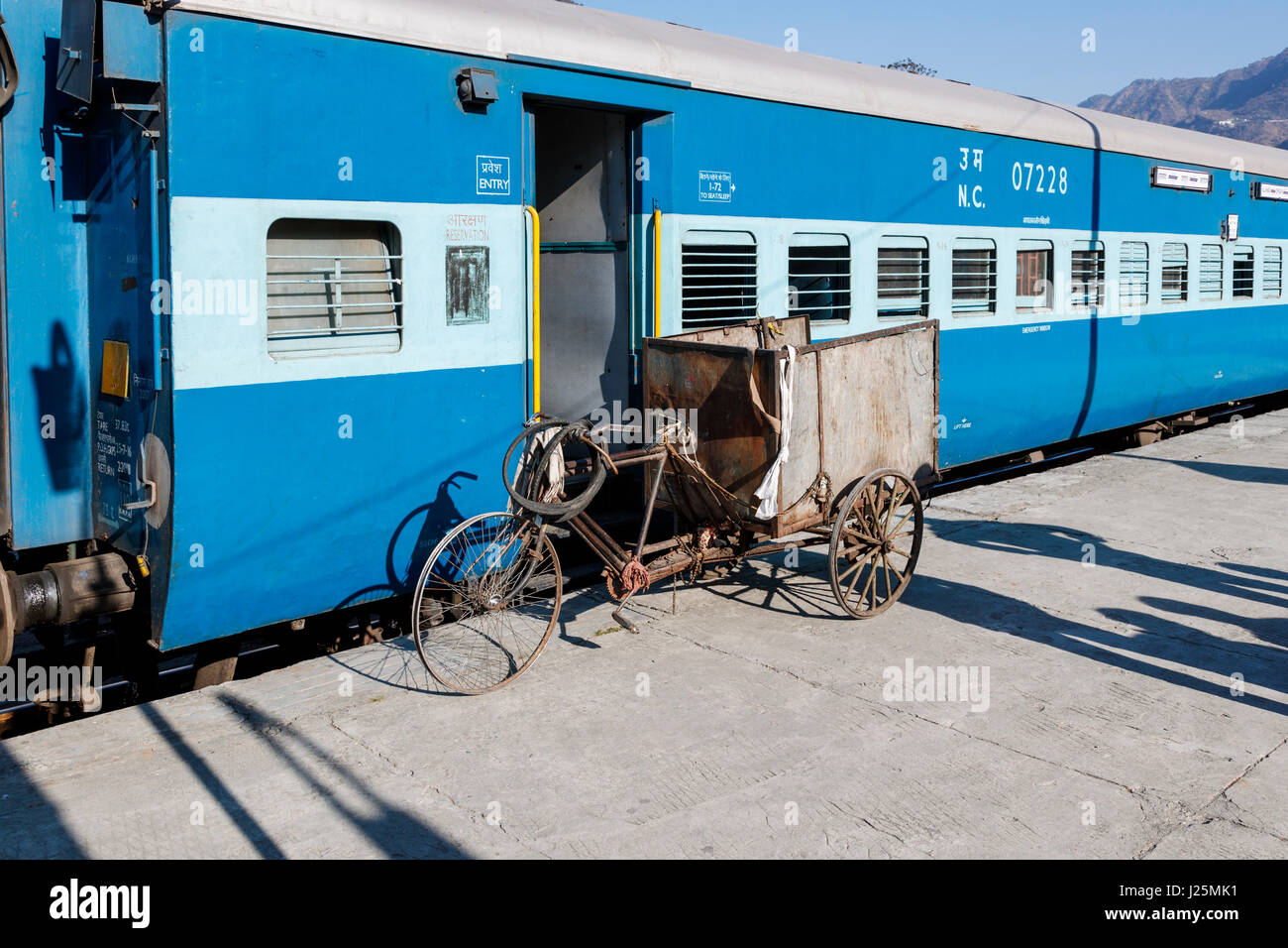 Battered, worn out rusty tricycle with no tyres next to a railway carriage at Kathgodam Station, Nainital District, - Stock Image