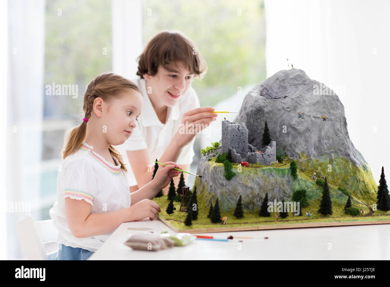 Children work on model building school project. Kids build miniature scale model mountain for geography class. Extracurricular - Stock Image