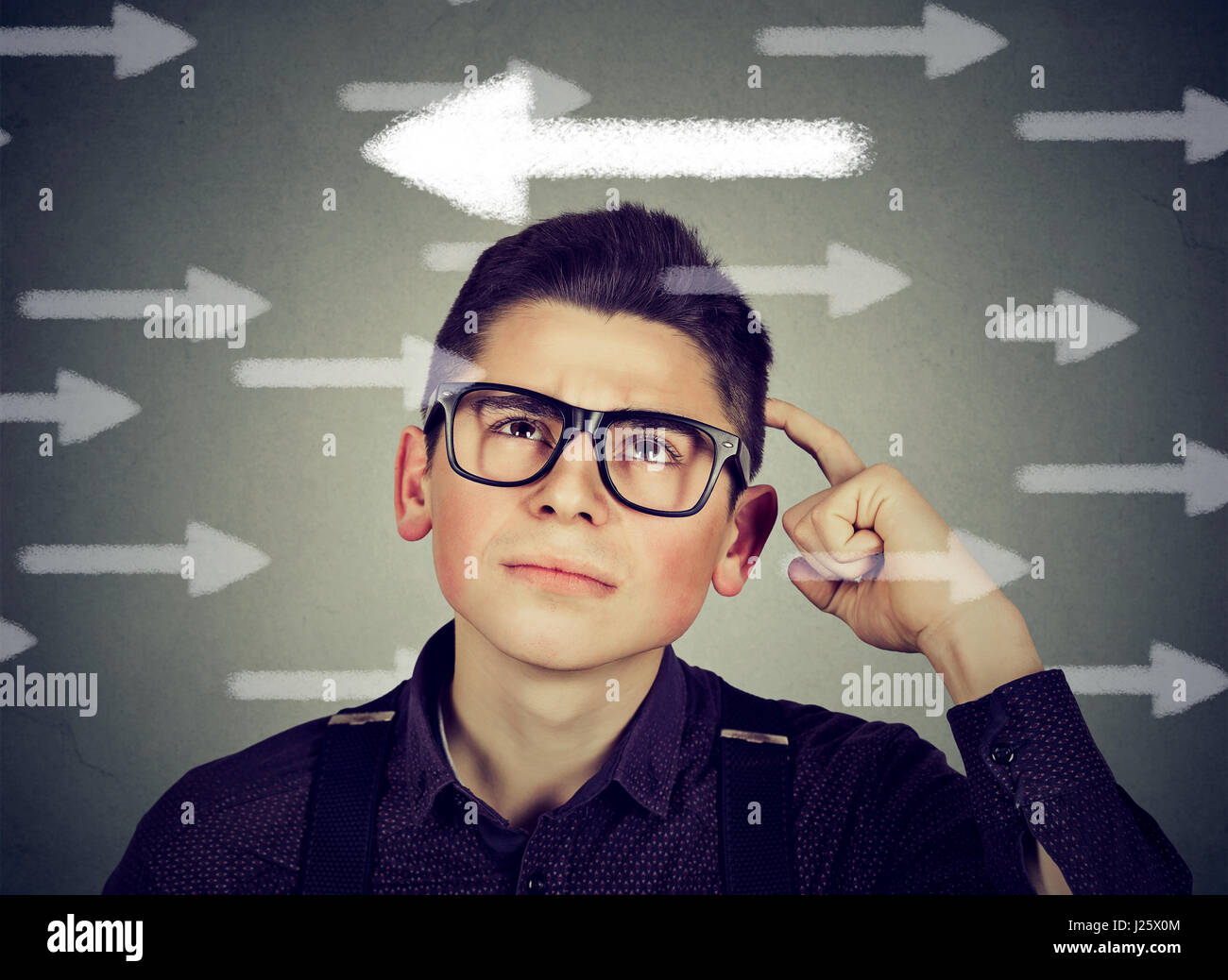 Young man in glasses has a second thought choice - Stock Image