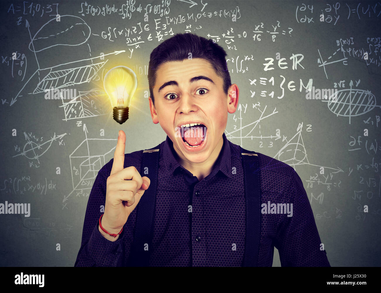 smart student with bright idea light bulb and high school maths and science formulas on blackboard background - Stock Image