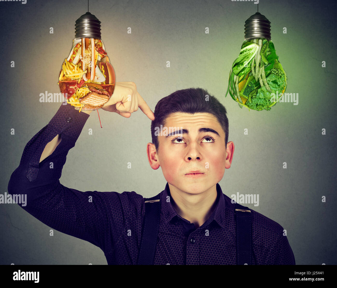 Diet choice healthy nutrition concept. Perplexed man thinking looking up at junk food and green vegetables light - Stock Image