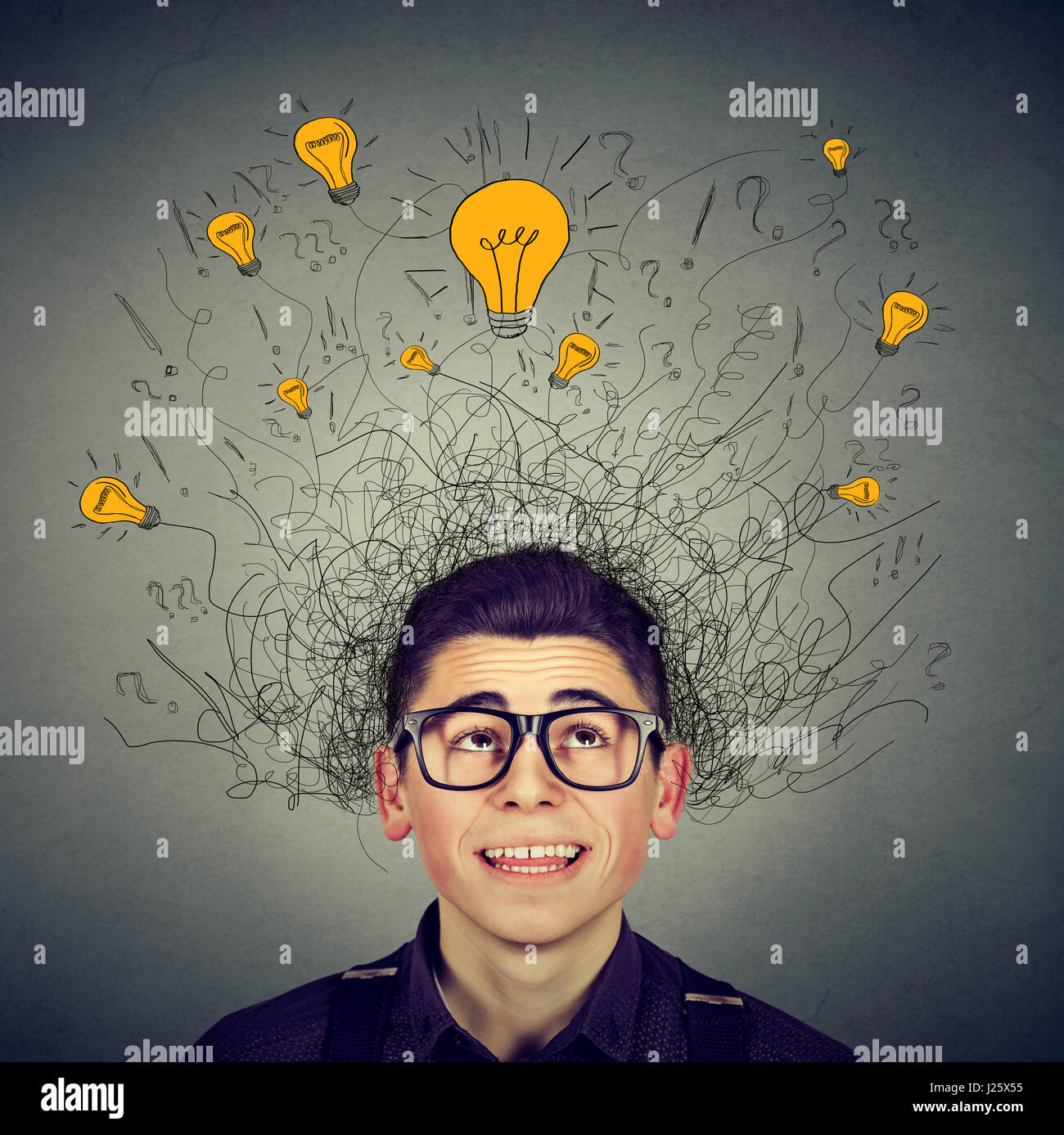Brain connections. Excited man with many ideas light bulbs above head looking up isolated on gray wall background. - Stock Image