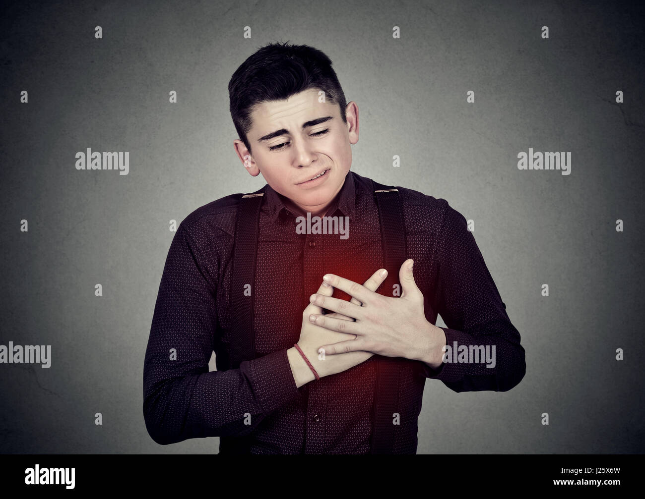 Adult man suffering from severe sharp heartache, chest pain. Heart disease concept - Stock Image