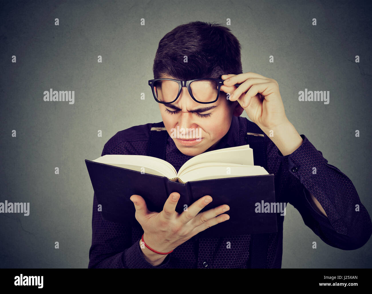 Closeup young man with eye glasses trying to read book, having difficulties seeing text, has sight problems. Eyesight - Stock Image