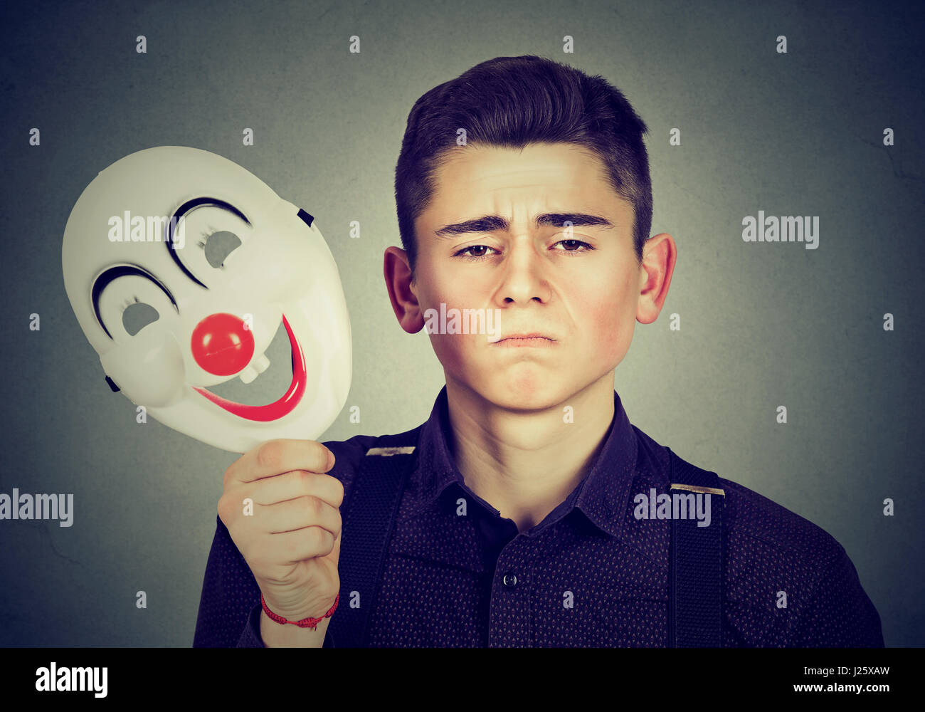 Young sad man taking off happy clown mask isolated on gray wall background. Human emotions. Split personality concept - Stock Image