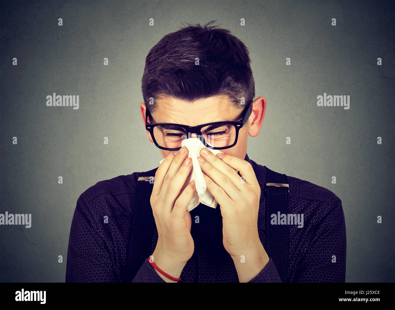 Young man in glasses sneezing in a tissue blowing his runny nose - Stock Image