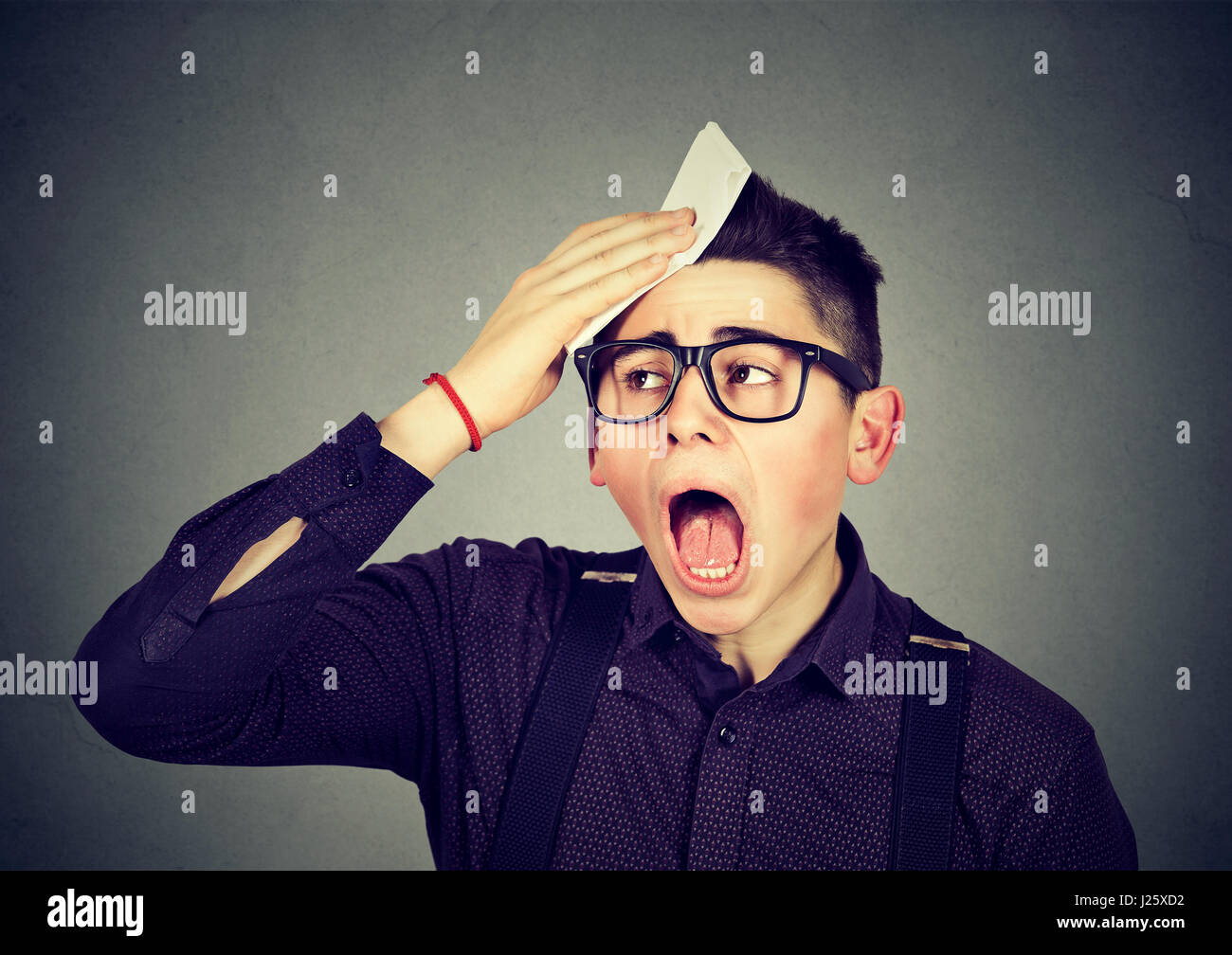 Tired man sweating isolated on gray background - Stock Image