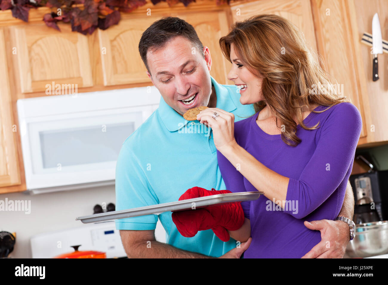 A beautiful woman baking cookies with her husband in the kitchen ...