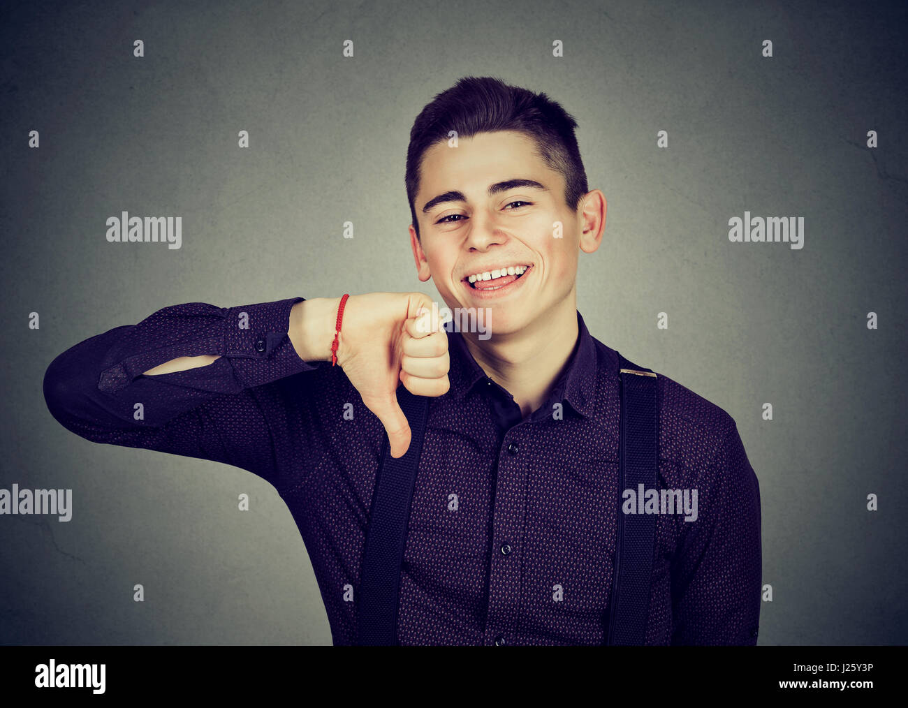 sarcastic man showing thumbs down hand gesture happy someone made mistake isolated on gray background. Human emotion, - Stock Image