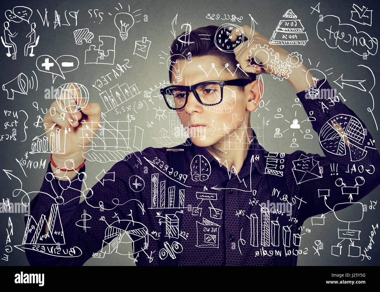 Smart thoughtful guy writing high school maths and science formulas on blackboard - Stock Image