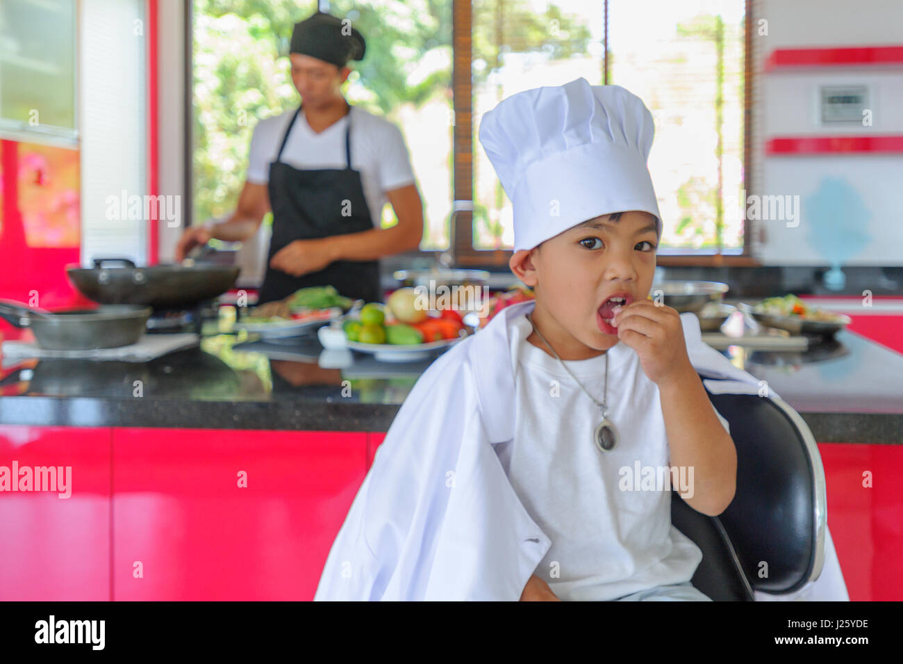 Cute little Thai boy in chef's hat and tunic sitting on a high chair in a modern style home kitchen. Dad is - Stock Image