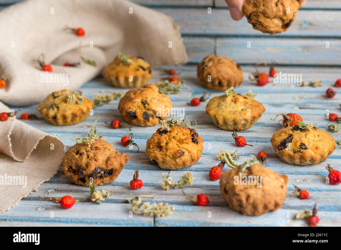 Fresh homemade delicious carrot muffins with raisins and dried fruits on a wooden background - Stock Image