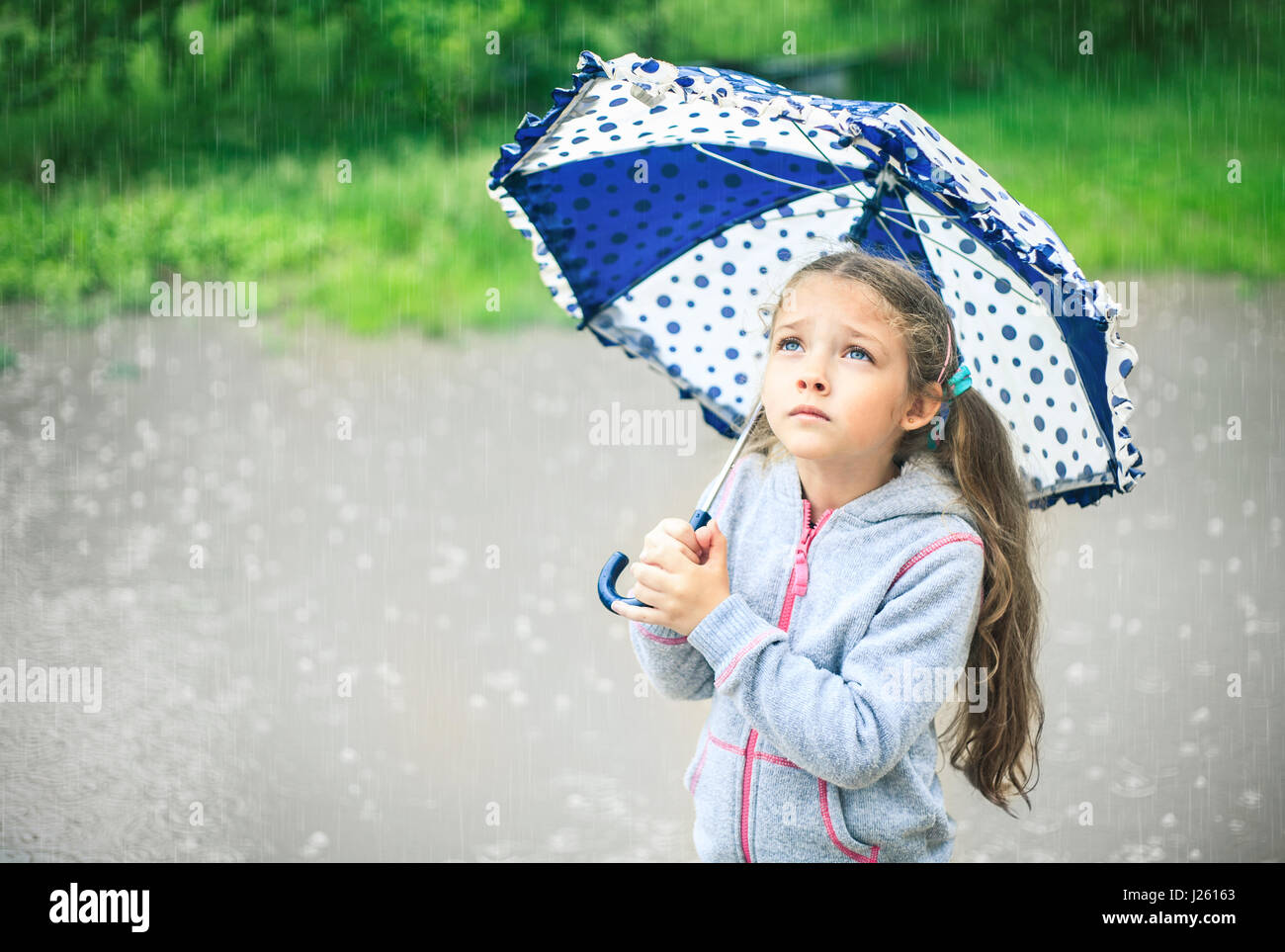 Portrait of a cute sad girl with an umbrella in the rain ...