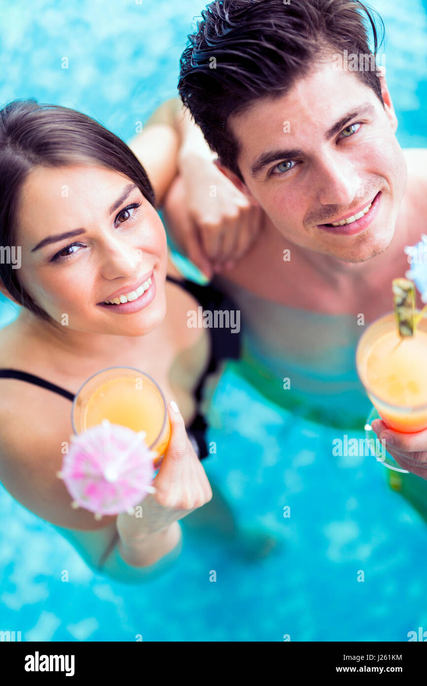 Portrait of a beautiful young couple smiling and drinking a cocktail in a pool - Stock Image