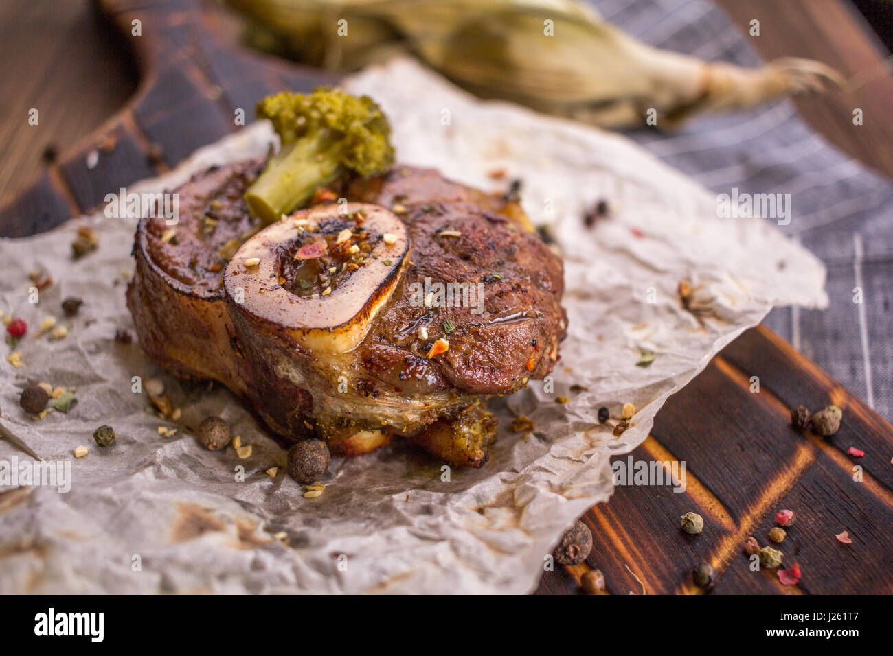 Baked lamb knee and close-up on a wooden board - Stock Image