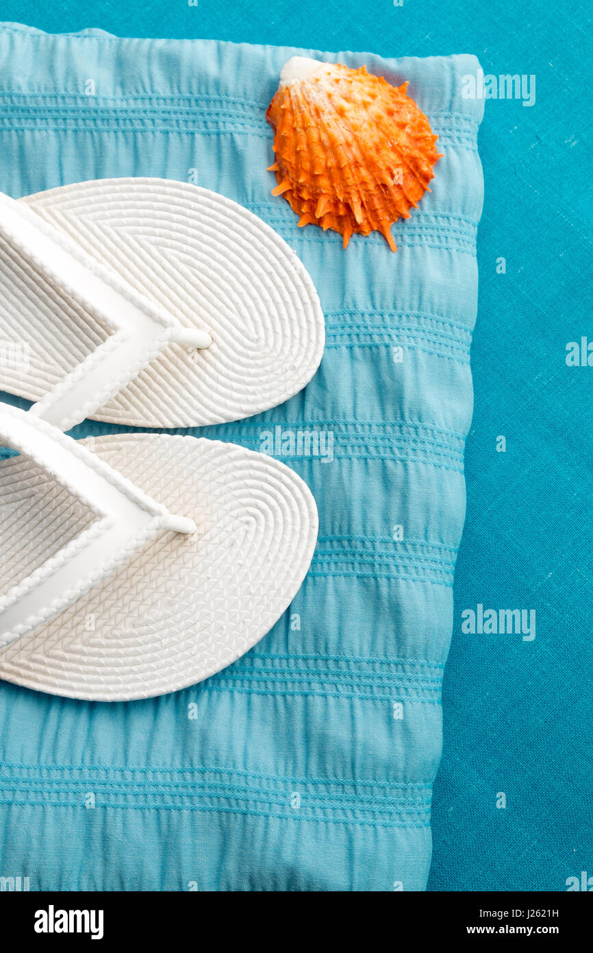 Flip flop near seashell on blue background. Top view - Stock Image