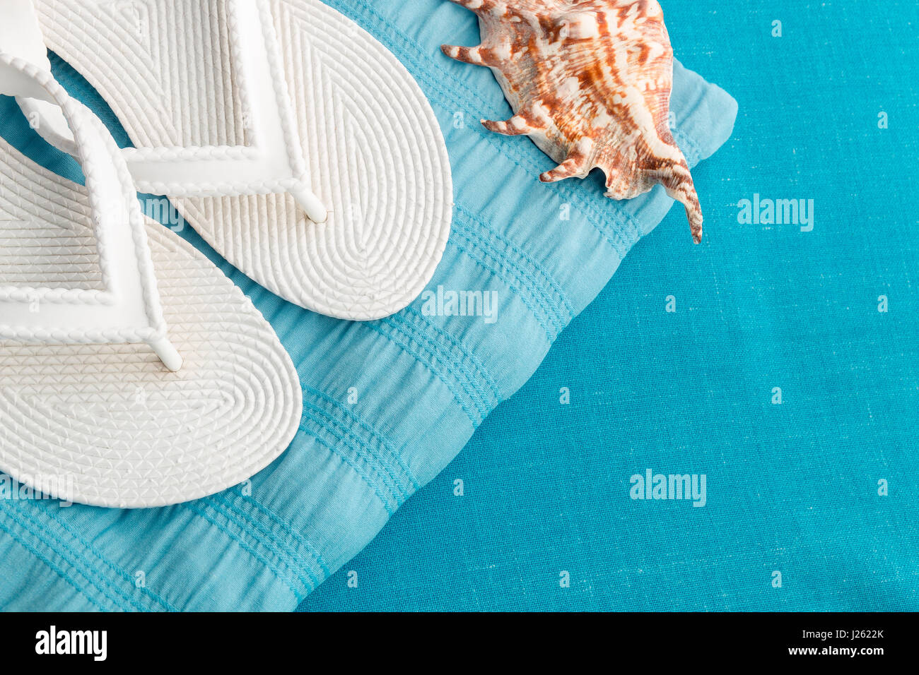6f4d04829 White flip flop near seashell on blue background. Top view Stock ...