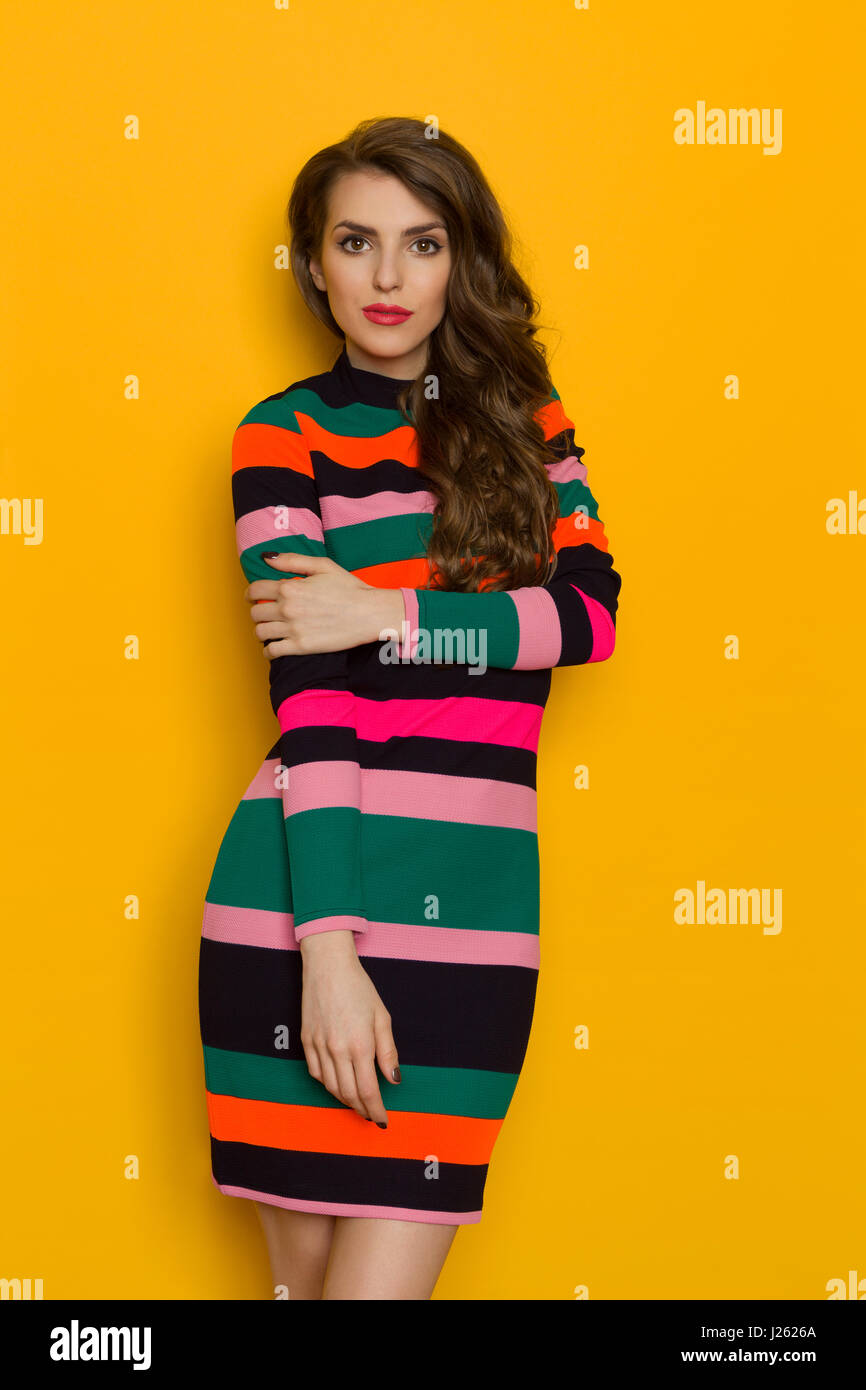 Beautiful young woman in colorful vibrant striped mini dress is posing against yellow background. Three quarter - Stock Image