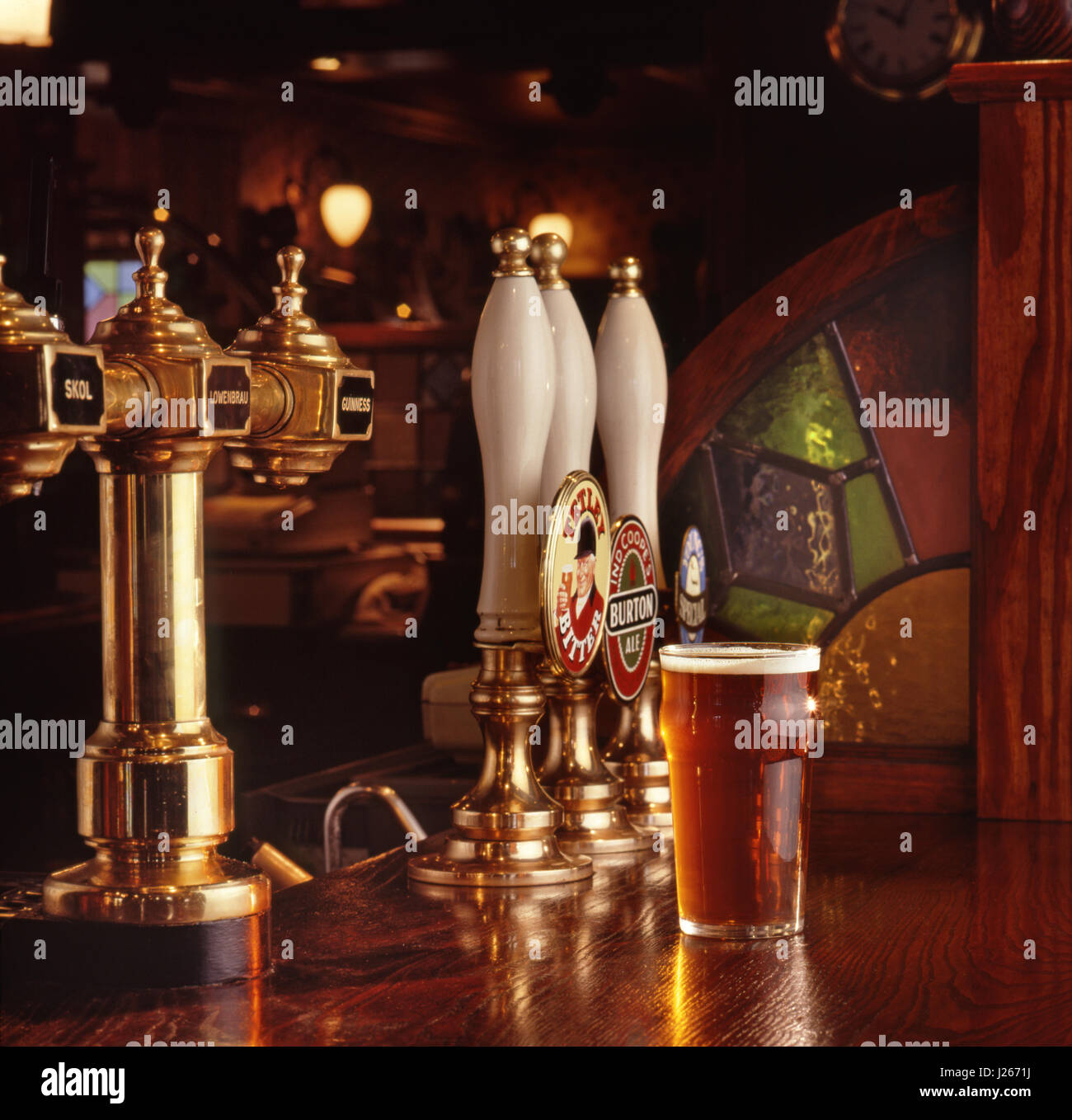 Pint of bitter served on the wooden bar surface of a warm, typical, traditional inviting English public house, with - Stock Image