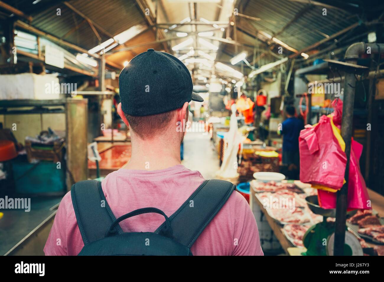 Young traveler with backpack in food market in Chinatown - Kuala Lumpur, Malaysia - Stock Image