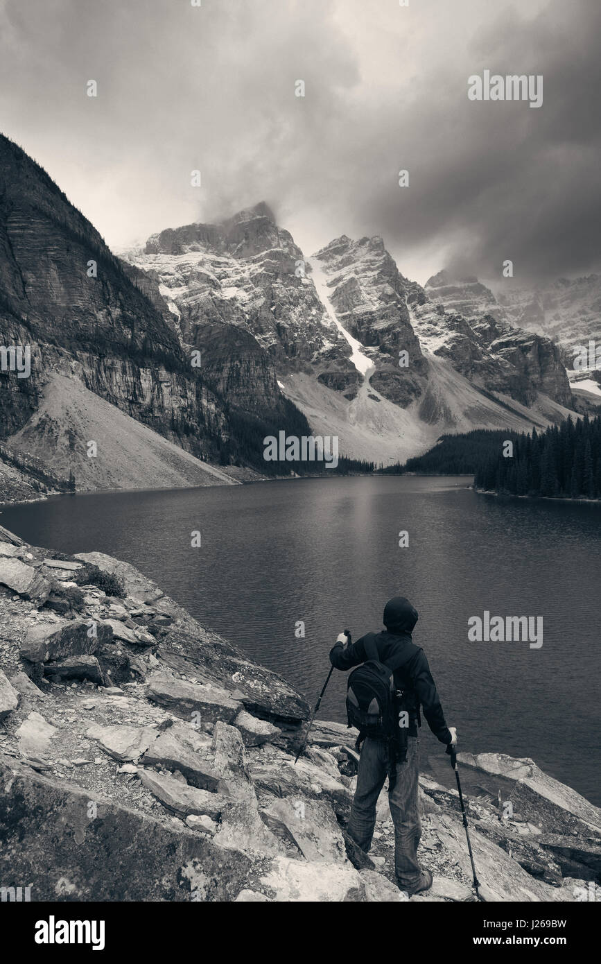 Hiker in Moraine Lake with snow capped mountain of Banff National Park in Canada Stock Photo