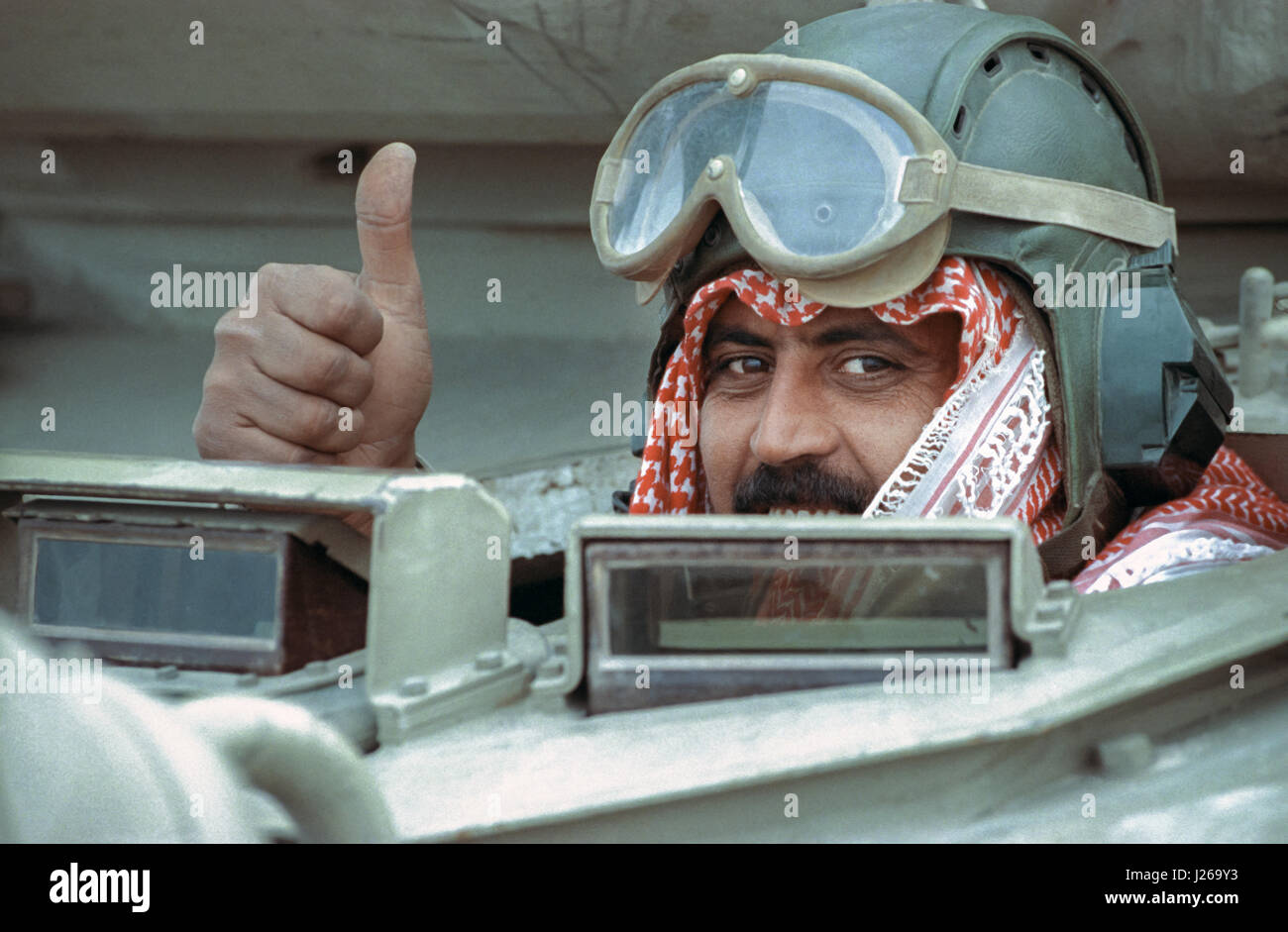 A Qatari tank soldier gives the thumbs up iafter leading coalition forces in the recapture of the city following - Stock Image