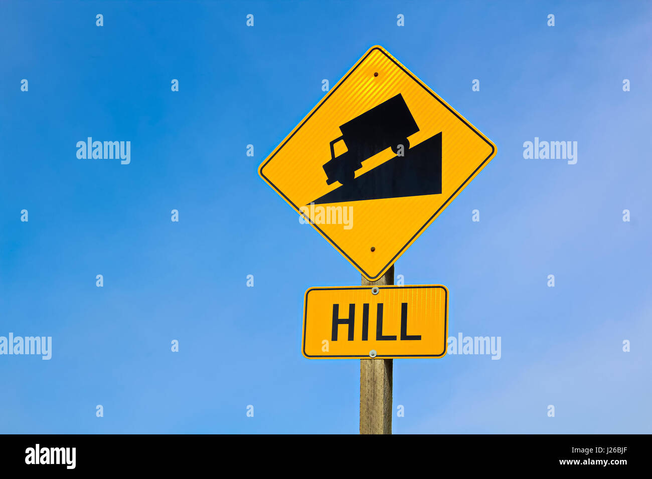 Approaching hill sign along highway. - Stock Image