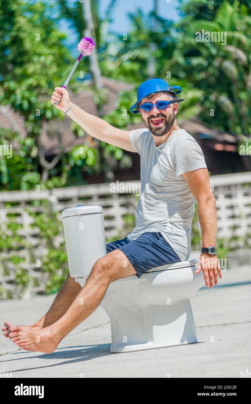 The bearded man in goggles astride the toilet, which is installed in the middle of the street. Toilet brush in his - Stock Image