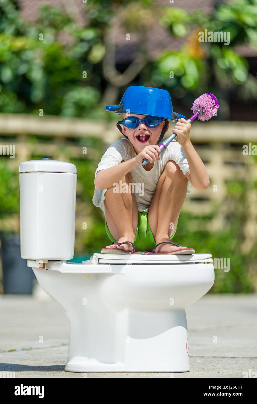Absurd picture: cute boy in goggles sitting on the toilet, which is installed in the middle of the street. Pan on - Stock Image