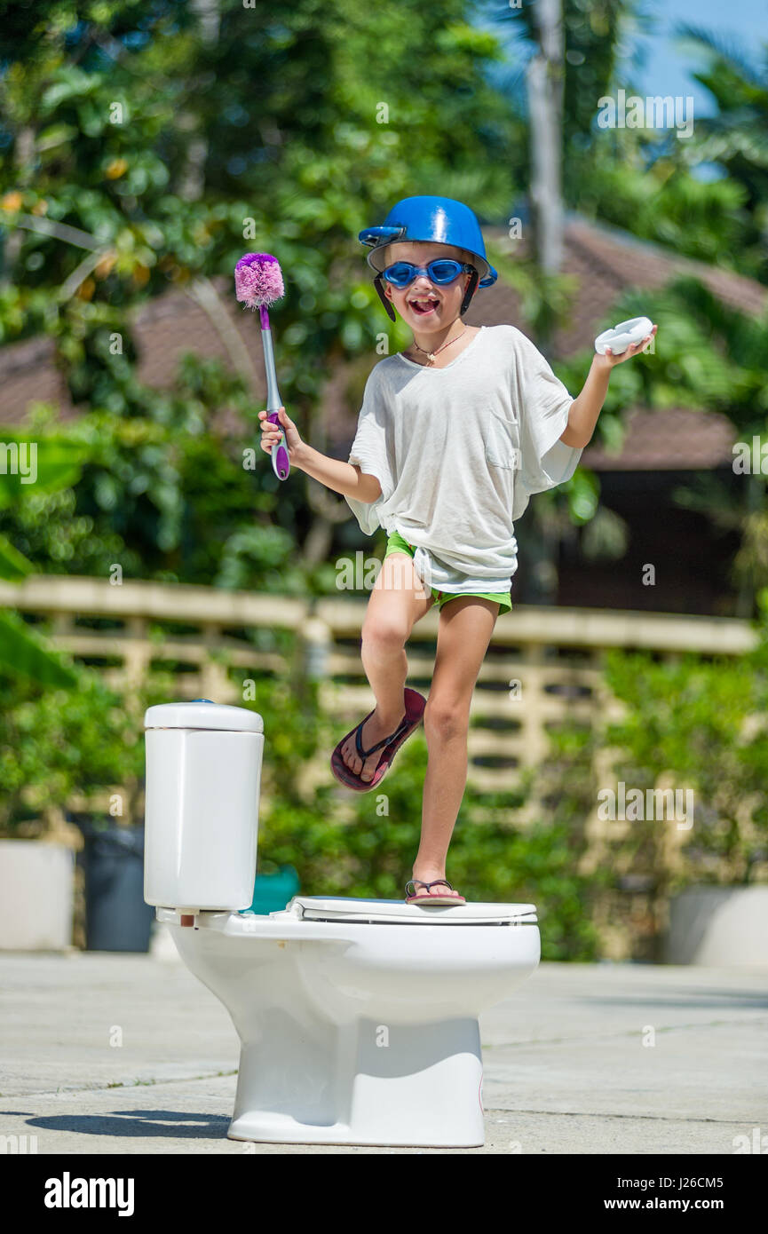 Absurd picture: cute boy dancing on the toilet, which is installed in the middle of the street. Pan on his head - Stock Image