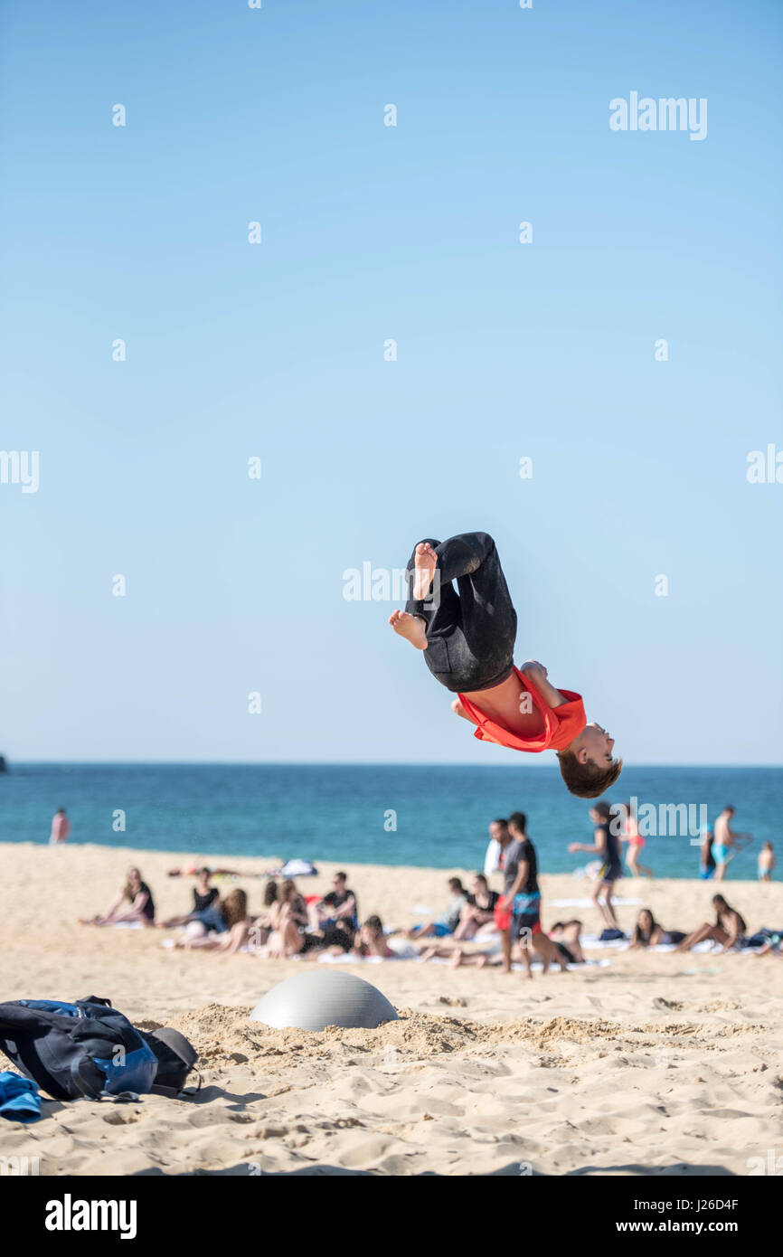 38bfb5c48f78e9 Kids are jumping very high on a beach and doing flip overs turning in the  air acrobatic jumps