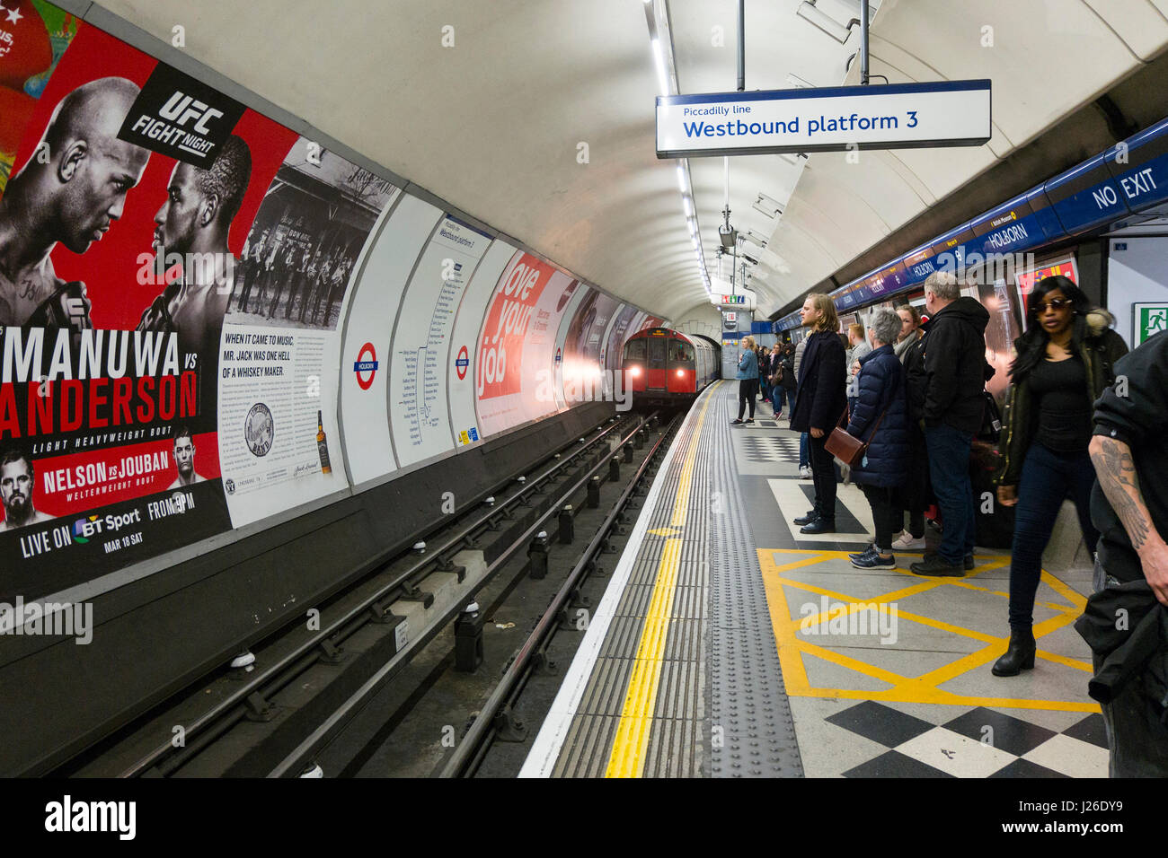 People waiting for the Piccadilly Line metro train to arrive at Westbound platform 3 of Holborn tube station, London, - Stock Image