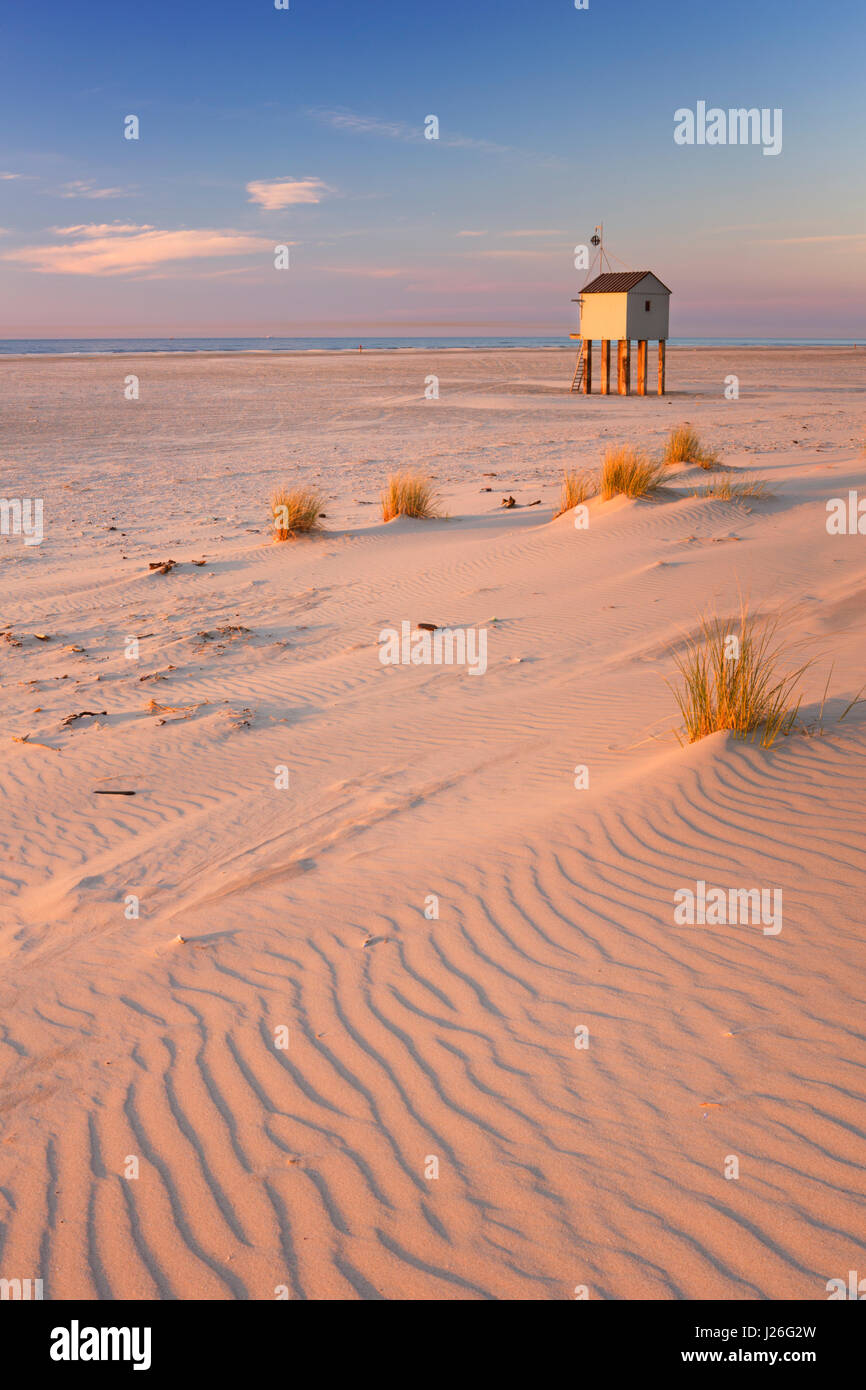 Refuge hut on the beach of the island of Terschelling in The Netherlands. Photographed at sunset. - Stock Image