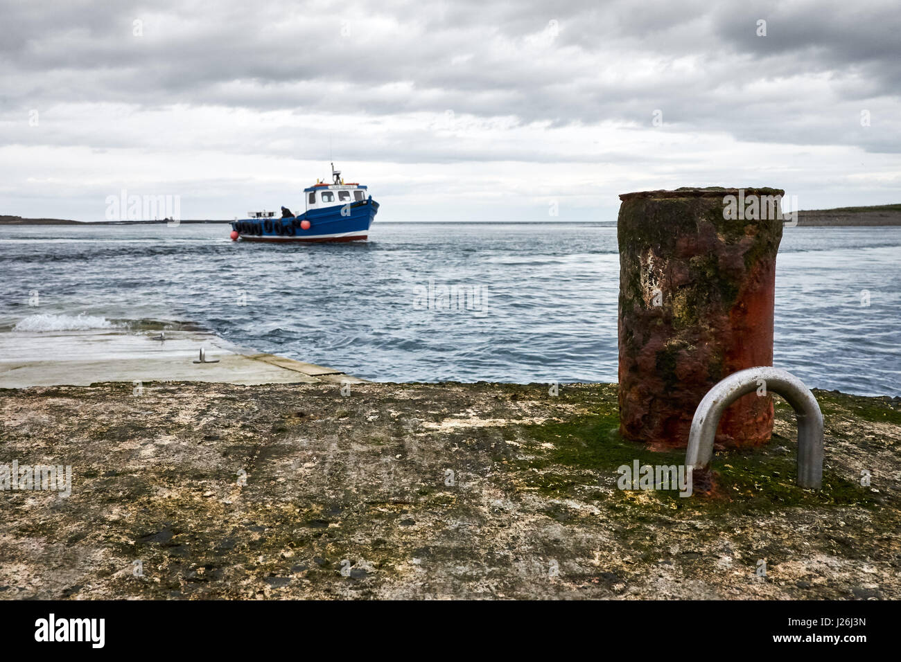A small passenger motor boat approaches a slipway under grey skies toward a post and eyelet to tying off. - Stock Image
