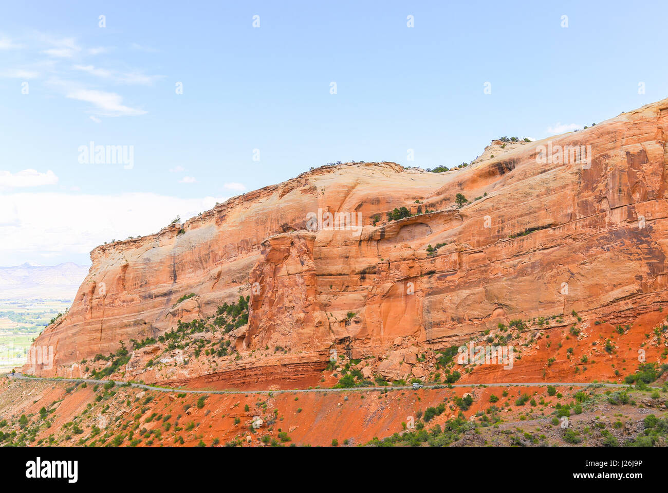 Cars driving on the Rim Rock Drive, the road going through the Colorado National Monument, in front of a red cliff. Stock Photo