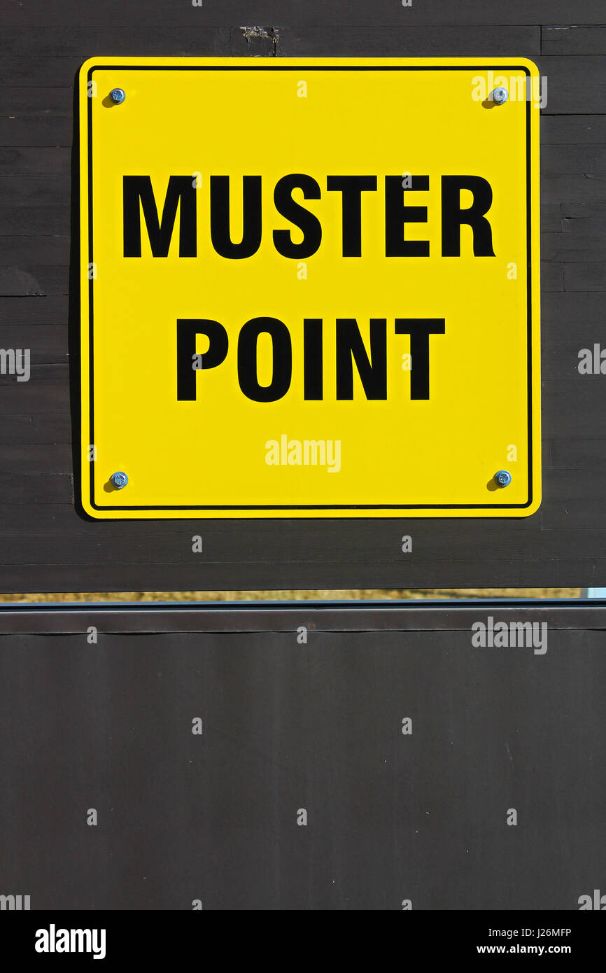 Muster assembly point sign on a wooden wall. - Stock Image
