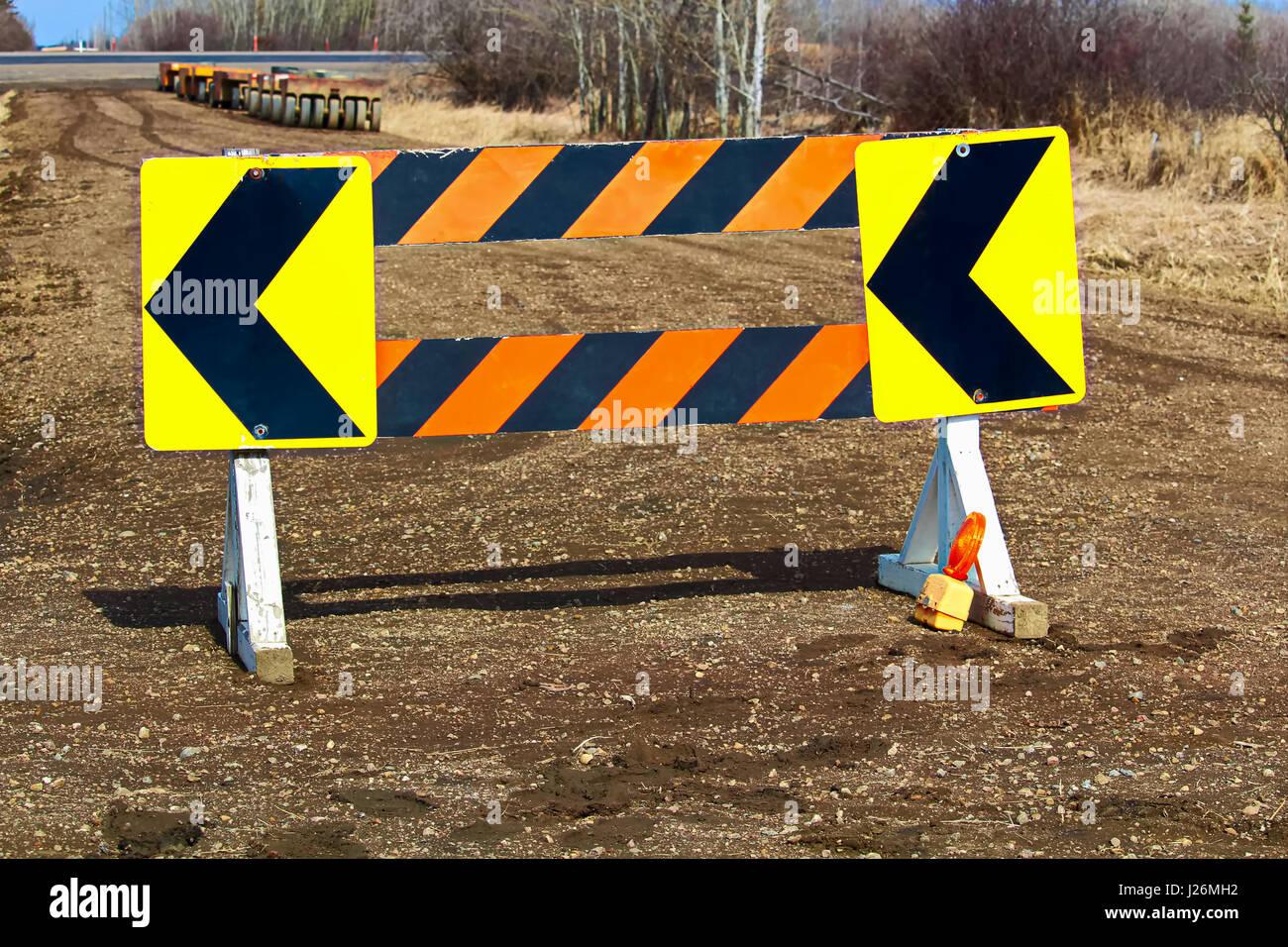 Detour construction barricade along a gravel road. - Stock Image
