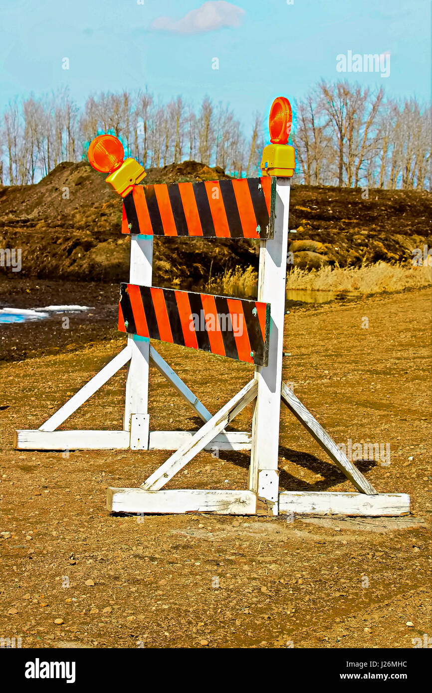 A construction barricade on a gravel road. - Stock Image