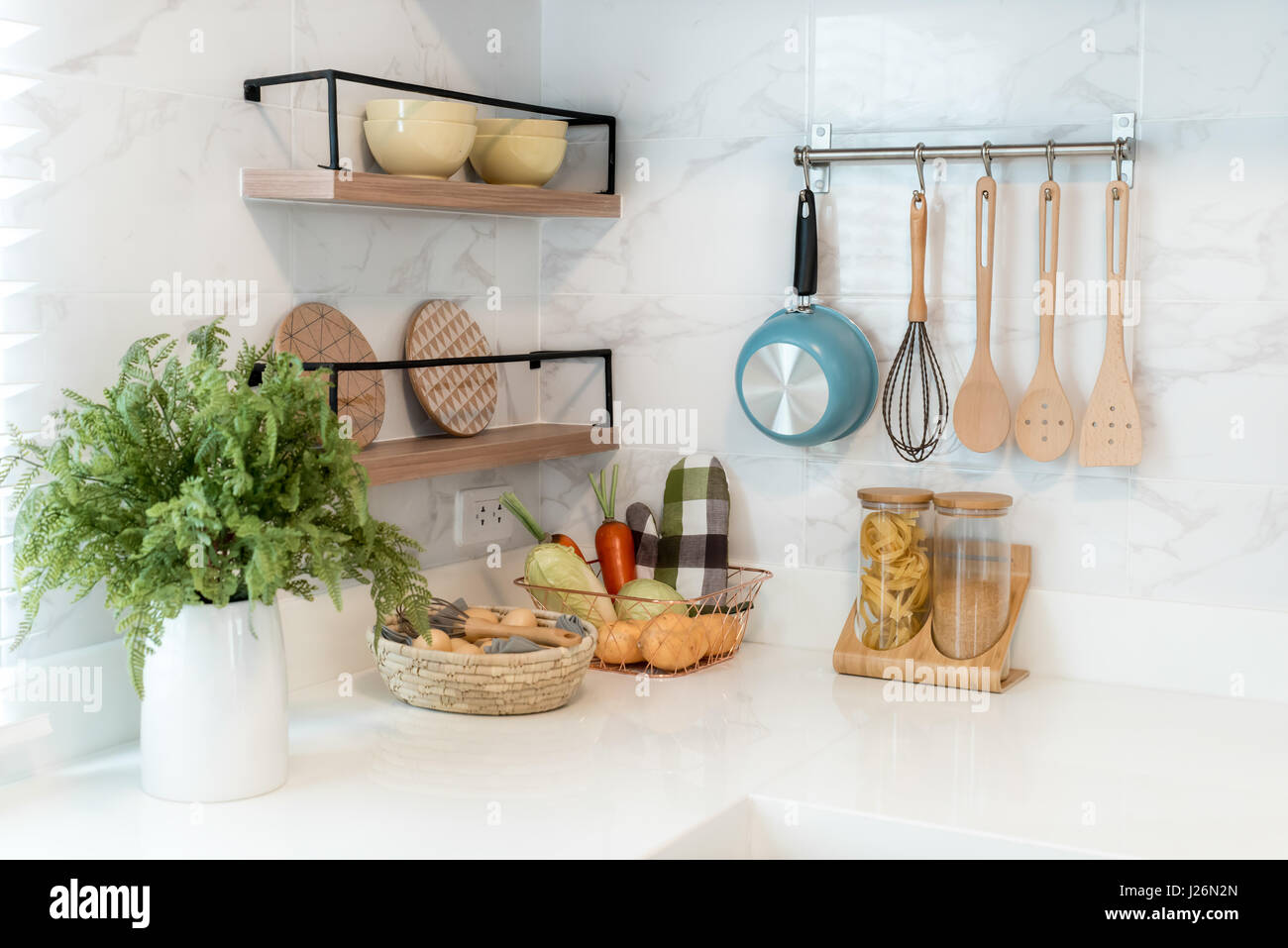 Kitchen wood utensils, chef accessories. Hanging copper kitchen with white tiles wall. - Stock Image