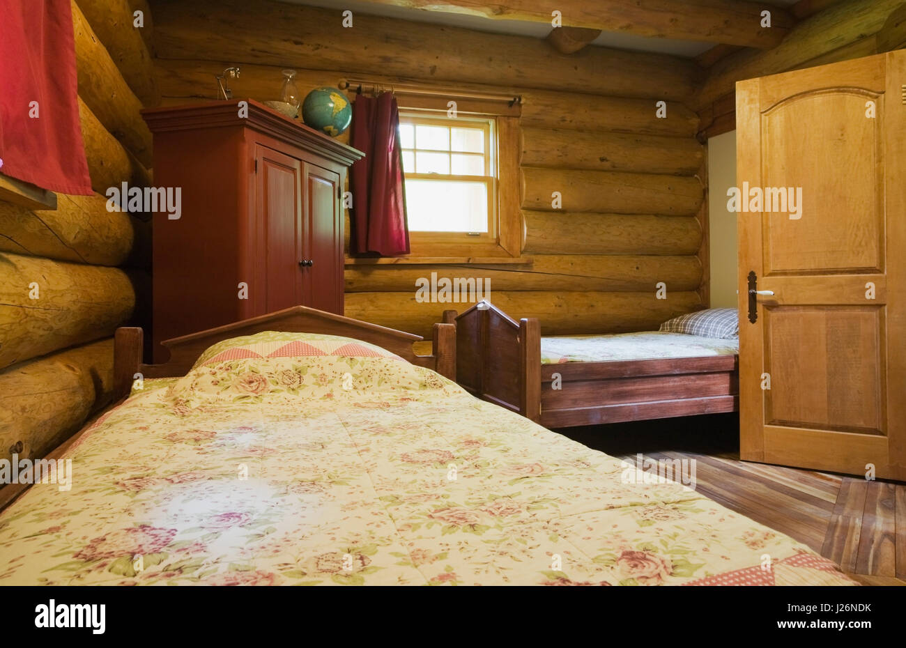 Guest bedroom inside a 2003 built cottage style residential log home - Stock Image