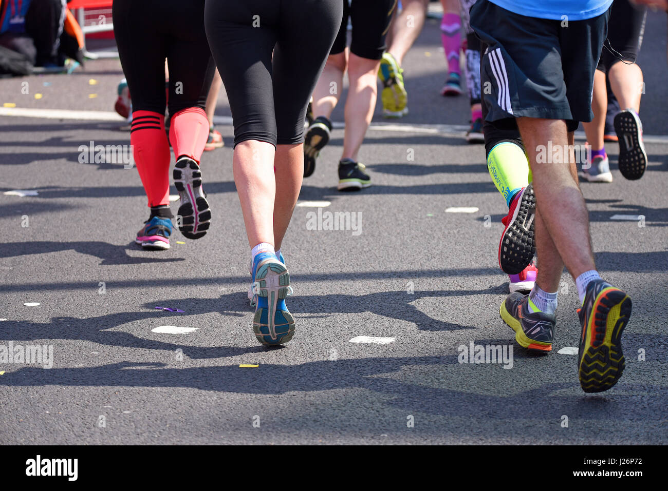 Legs of runners racing in the 2017 Virgin London Marathon after crossing Tower Bridge and alongside the Tower of - Stock Image