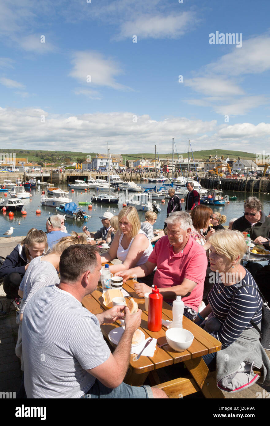 West Bay Dorset - english tourists eating outdoors at a cafe - concept - Staycation; West Bay, Dorset UK - Stock Image