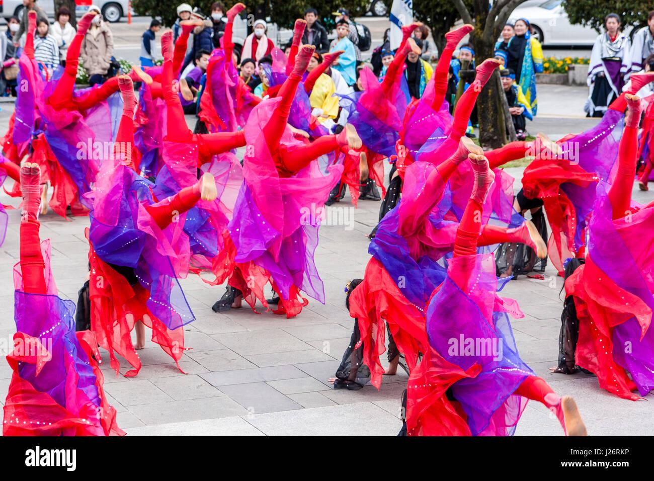 Hinokuni Yosakoi dance Festival. Children's Girl dance team, all dressed as fairies in red flayed costumes, somersaulting Stock Photo