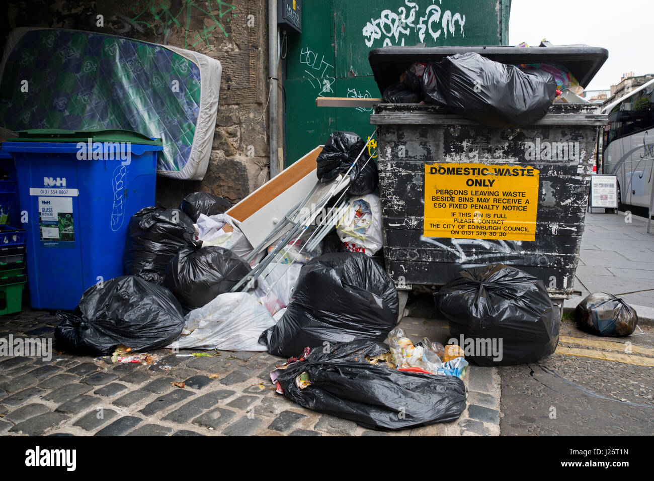 Rubbish bags left beside a bin which has a sign that reads, Persons leaving waste beside bins may receive a £50 - Stock Image