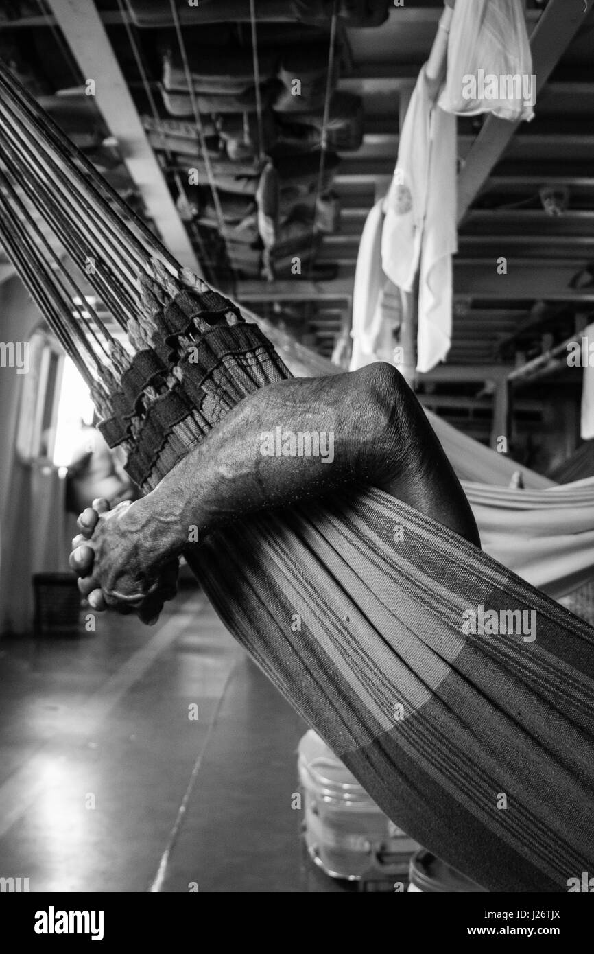 Man rests in hammock while going up the Amazonas river, in Brazil, whit a ferry boat. - Stock Image